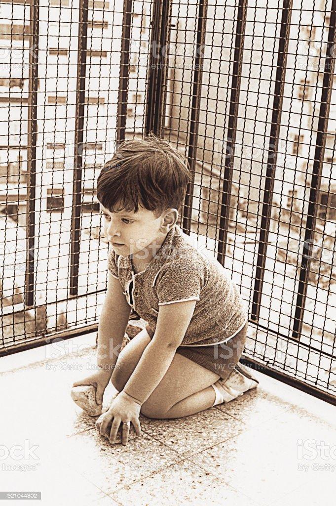 Vintage sepia toned image of a cute kid kneeling stock photo