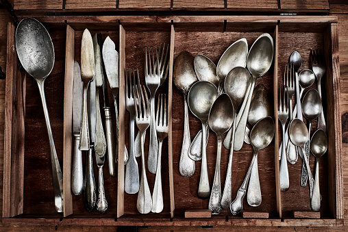 Vintage service cutlery inside a rustic wooden box.