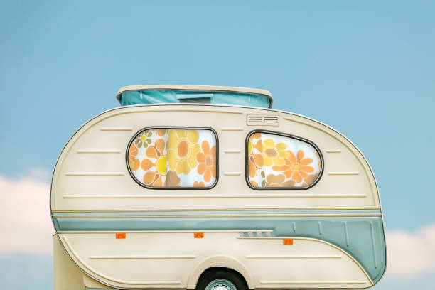 Vintage seventies white caravan in front of a blue sky with clouds stock photo