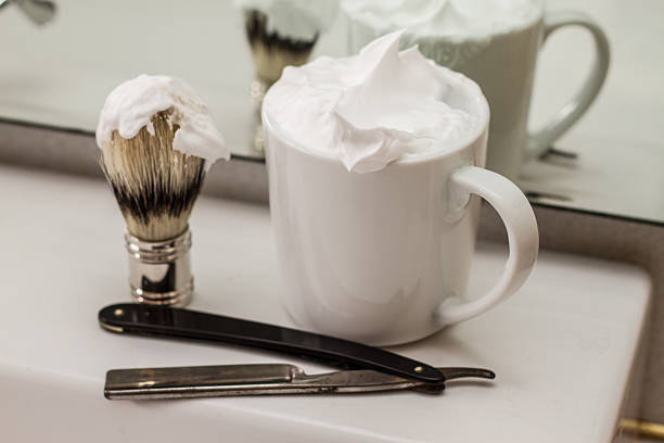 Vintage shaving cream, straight razor, and cup in the mirror Cup full of shaving cream with a brush and vintage straight razor in bathroom mirror on sink. shaving brush shaving cream razor old fashioned stock pictures, royalty-free photos & images