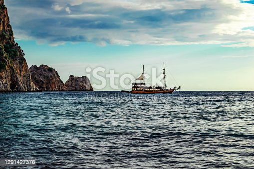 Vintage ship on the sea horizon in Alanya (Turkey) on a cloudy day. Beautiful seascape with rocks in the water and a large cloud in the blue sky over the smooth ripples of the Mediterranean Sea