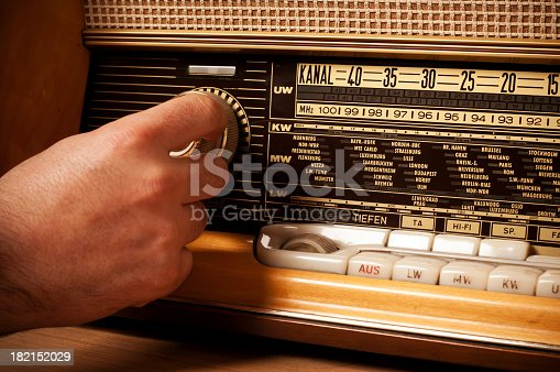istock Vintage short wave radio with person's hand on the tuner 182152029