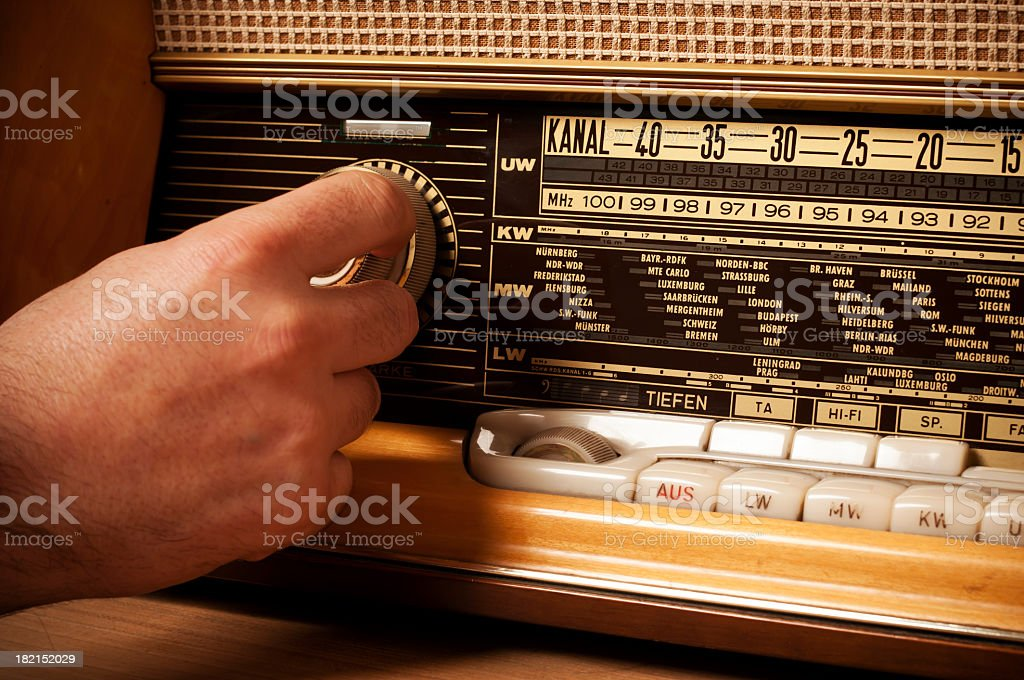 Vintage short wave radio with person's hand on the tuner stock photo