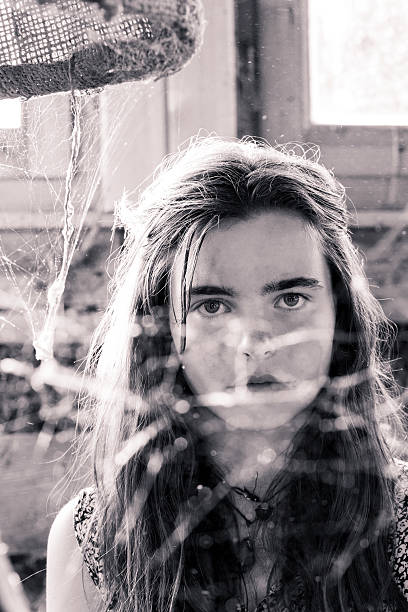 vintage shot of a teenage girl behind a spider web stock photo