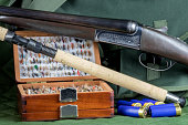 Old shotgun with fishing rod and fly box and cartridges with game bag on an outdoor coat