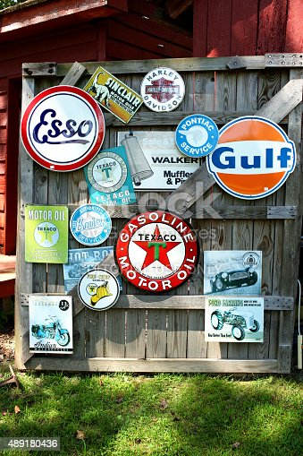 Gloucester, Va. USA  - August 16, 2015:   Hanging on an old barn door are vintage signs from the gas and oil industry including Texaco, Gulf, Esso, Buick and Pontiac, most signs from the American Motor industry.