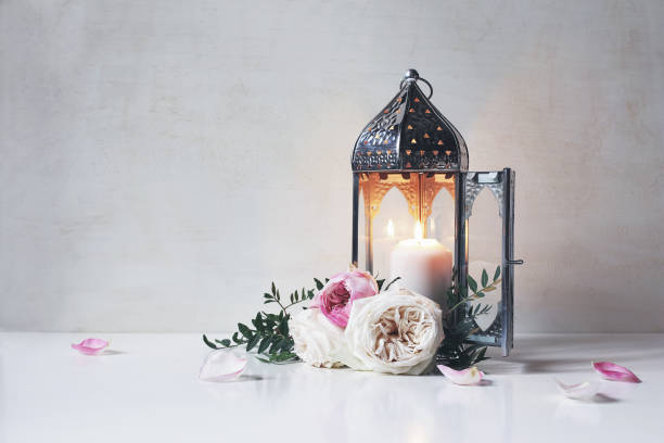 vintage silver moroccan, arabic lantern with glowing candle, green branches, rose flowers and pink petals on white table background. greeting card for muslim holiday ramadan kareem. shaby wall. - eid stock pictures, royalty-free photos & images