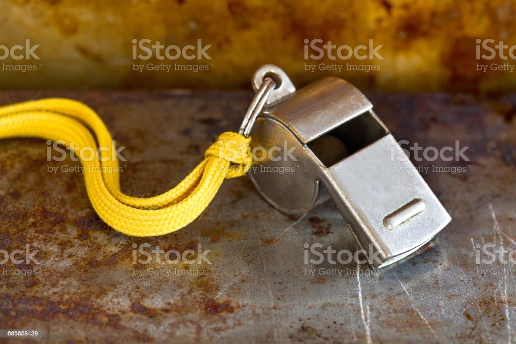Vintage silver whistle on rusty metallic background. Referee trainer sport competition tool instrument, start finish stopping game and attention moments equipment. Close-up photo stock photo