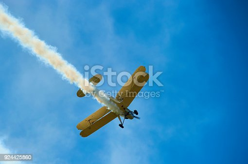Vintage single engine propeller biplane aircraft flying against sky - bottom view