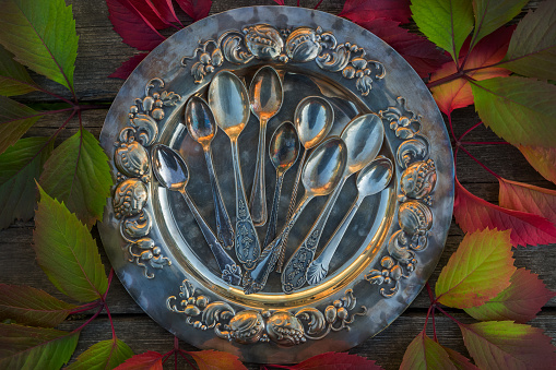 Vintage small spoons on vintage silver dish, tray. Vintage cutlery, kitchen utensils as a concept, idea on a wooden background with colorful vine leaves.