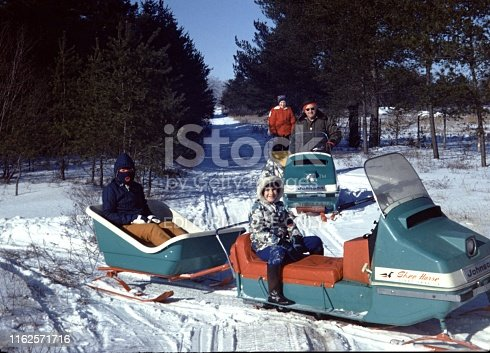 Wyoming, United States - January 01, 1976:  Vintage, authentic archival photograph of a family wearing heavy winter coats and smiling while posing outdoors on a snowmobile in Wyoming, United States, 1976