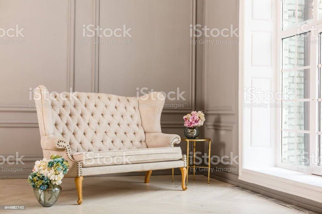 Vintage Sofa Of Soft Pink Color Decorated With Flowers And Greens Stands In  A Classic Room