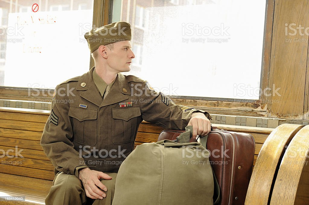 Vintage Soldier Sitting On Wooden Bench In Bus Station royalty-free stock photo