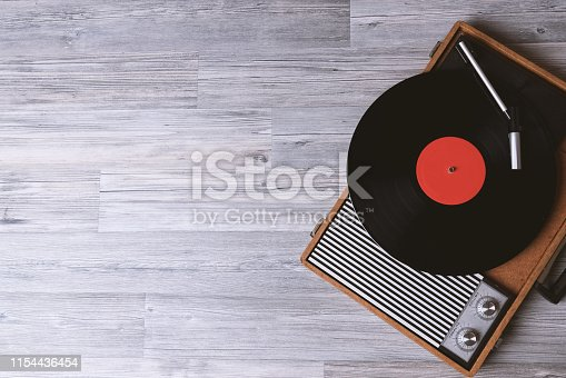 Turntable vinyl record player on the background of their gray wooden boards. Needle on a vinyl record. Black vinyl record,Sound technology for DJ to mix & play music.