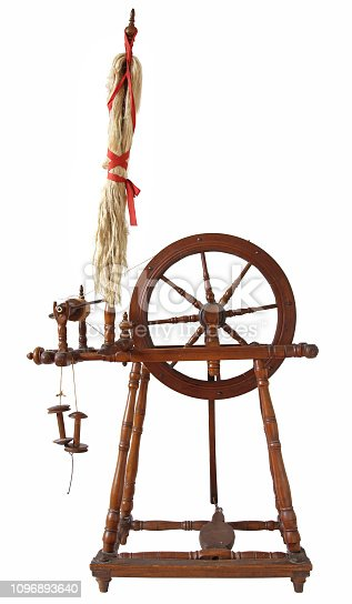 Vintage spinning wheal with yarns, isolated on white background