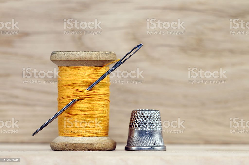 Vintage spool of thread with needle closeup on wooden background stock photo