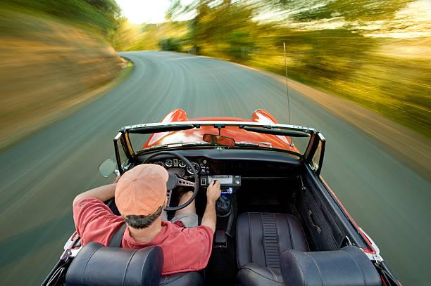 vintage sport auto auf der straße - alten muscle cars stock-fotos und bilder