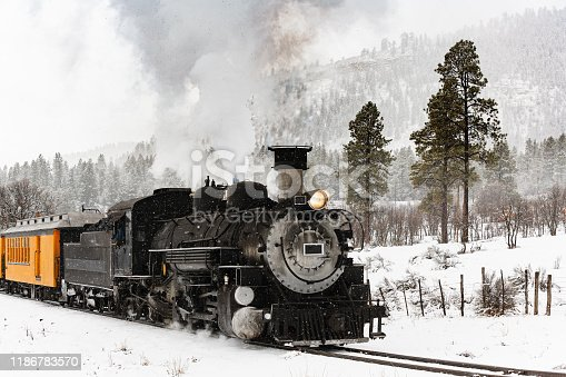 Vintage Railroad Steam Locomotive Pulling Passenger Cars in a Mountin Snow Storm.