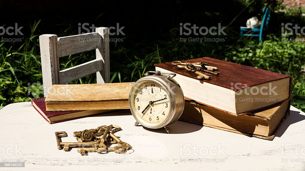 Vintage still life with old alarm clock, keys and books stock photo