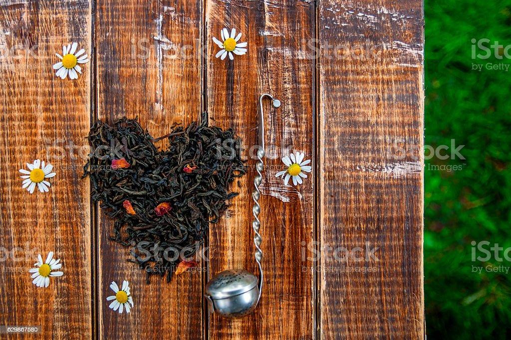 Vintage strainer near dry leaves of black tea stock photo