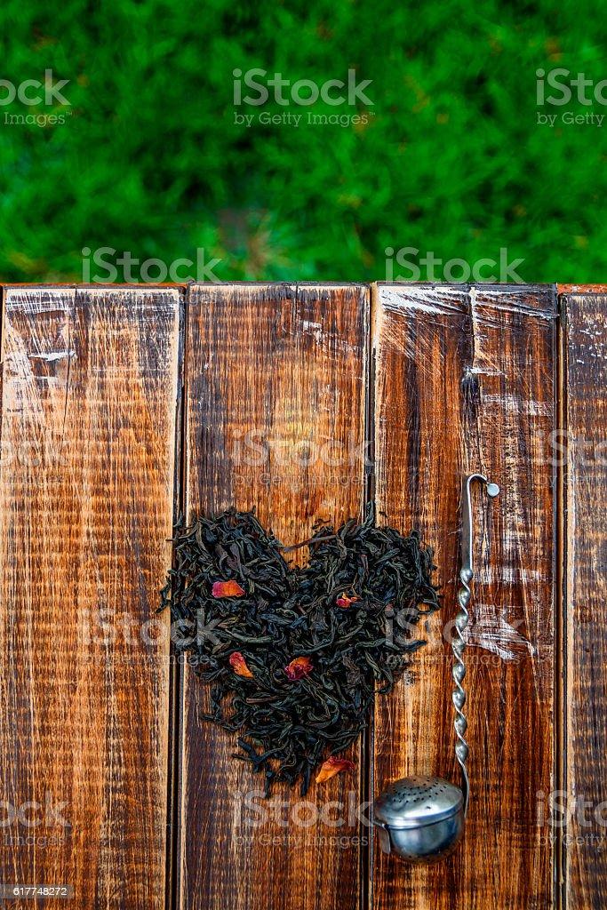 Vintage strainer near dry leaves of tea make in heart stock photo
