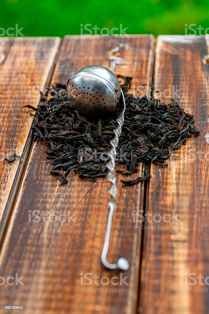 Vintage strainer with dry leaves of black tea on wooden stock photo