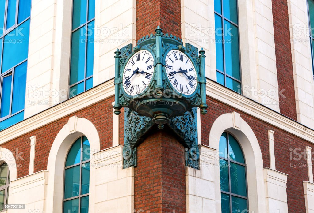 Vintage street clock hanging on a corner of brick building in Samara, Russia royalty-free stock photo