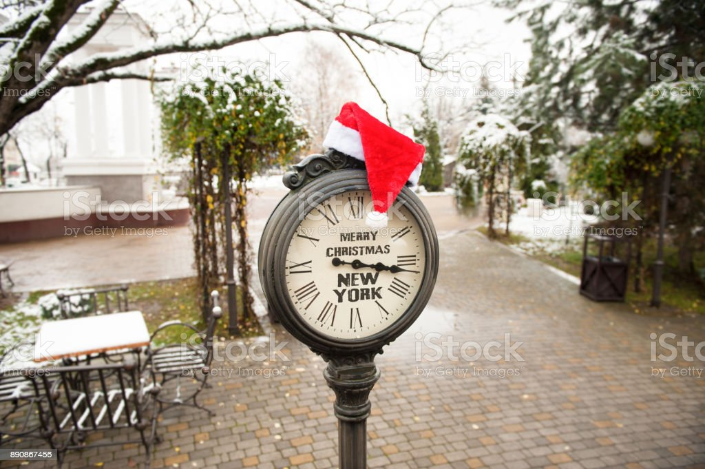 vintage street clock with text Merry Christmas New York and Santa Claus hat on them outdoor in new york central park stock photo