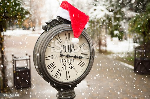 istock vintage street clock with title Happy New Year 2018 and Santa Claus hat on them with falling snowflakes 880753260
