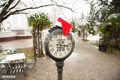 istock vintage street clock with title Happy New Year 2018 and Santa Claus hat on them in town park 882859938
