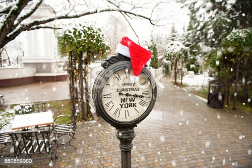 istock vintage street clock with title Merry Christmas New York and Santa Claus hat on them with falling snowflakes 882859960