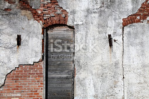 a old vintage stucco brick wall with  boarded wooden arched window