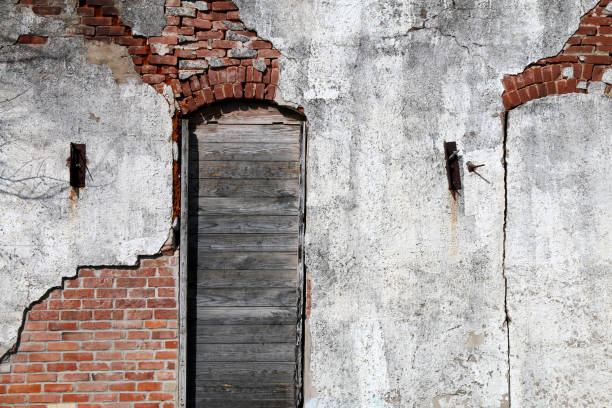 vintage stucco brick wall boarded wooden arched window stock photo
