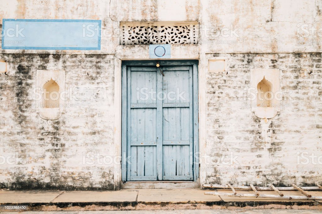 Céu e parede de tijolo de estilo vintage azul porta de madeira, casa indiana antiga - foto de acervo