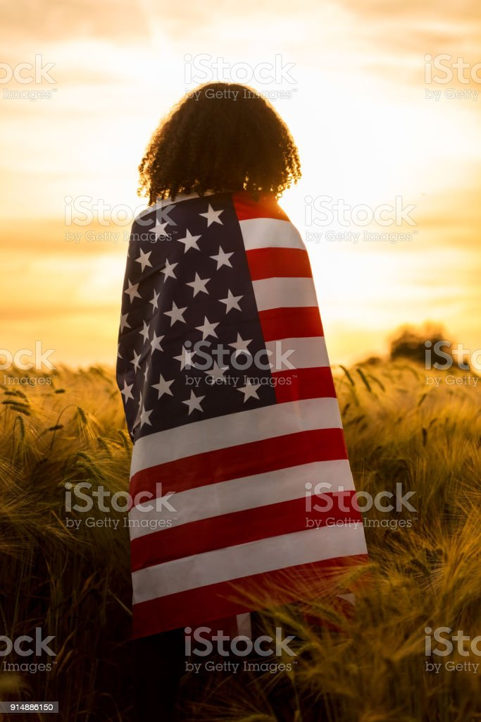 Vintage style photograph of mixed race African American girl teenager female young woman in a field of wheat or barley crops wrapped in USA stars and stripes flag in golden sunset evening sunshine stock photo