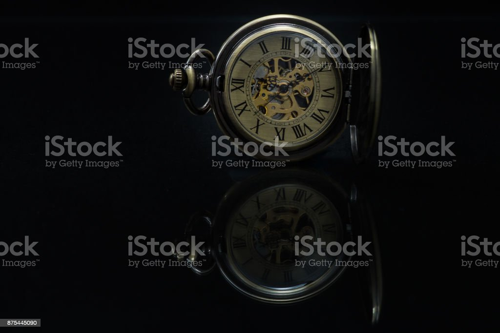 Vintage style pocket watch with reflection on black background. stock photo