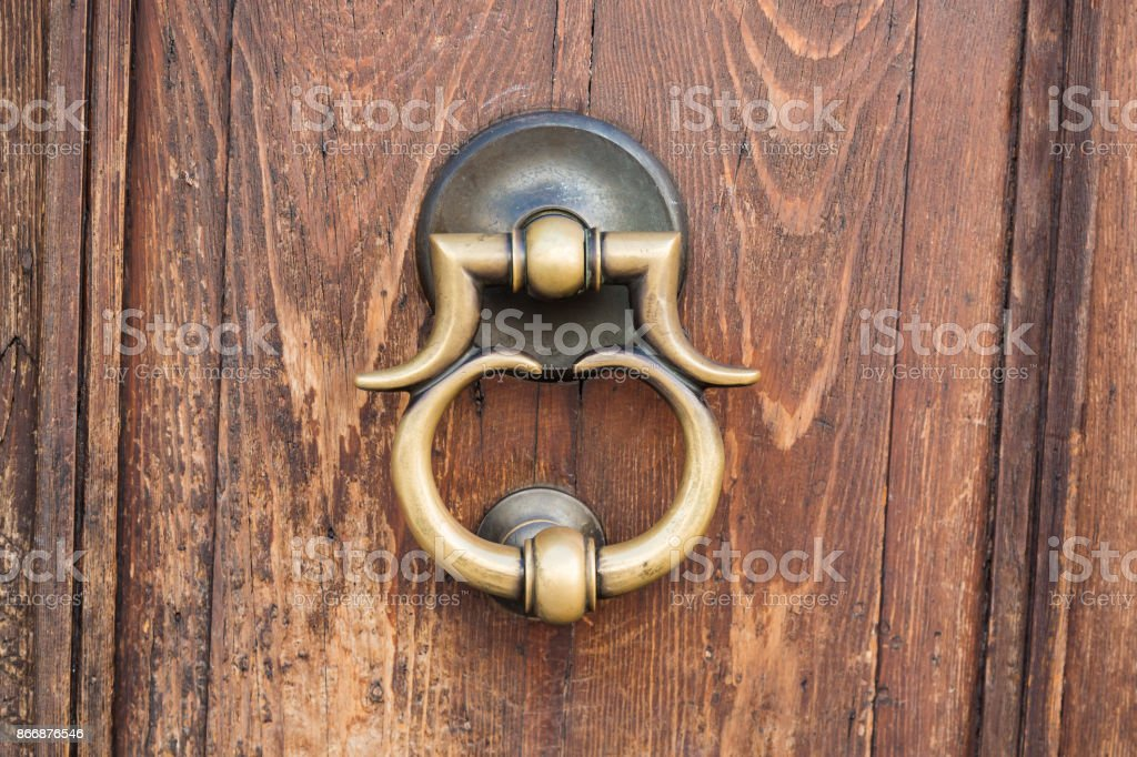 Vintage style retro bronze door handle or knocker with wooden door. Close up image stock photo