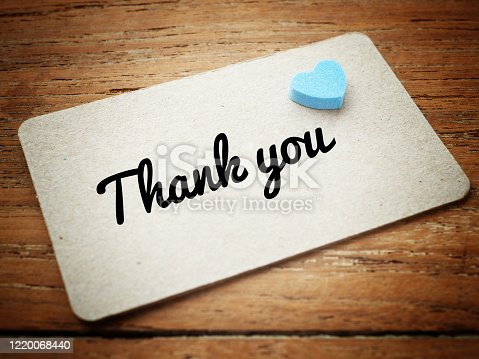 istock Vintage style, The words thank you and blue heart on brown paper. 1220068440
