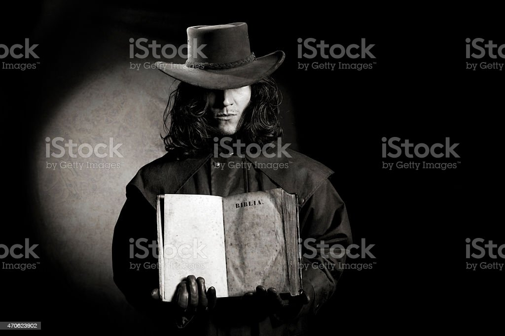 vintage style wild west gunslinger holding ancient bible book stock photo