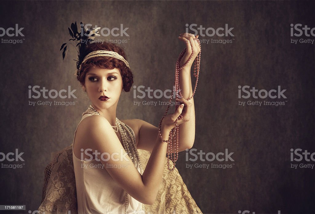 vintage style woman holding pearl necklaces stock photo
