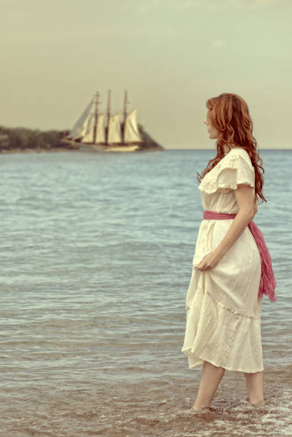 vintage style woman walking in ocean with tall ship portrait of vintage style woman walking in ocean with tall ship edwardian style stock pictures, royalty-free photos & images