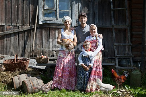 Vintage styled family portrait with some hens grazing in the grass.