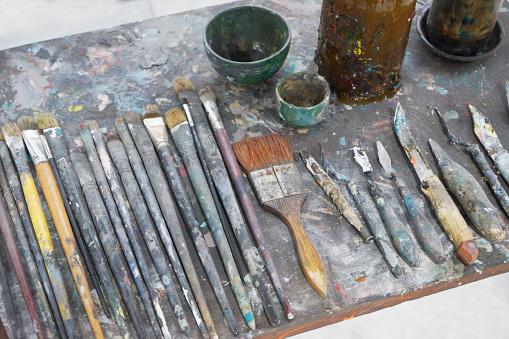 577949148 istock photo Vintage stylized photo of paintbrushes closeup and artist palett 1173572796