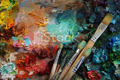 artists brushes and oil paints on wooden palette. Vintage stylized photo of paintbrushes closeup and artist palette. palette with paintbrush and palette-knife