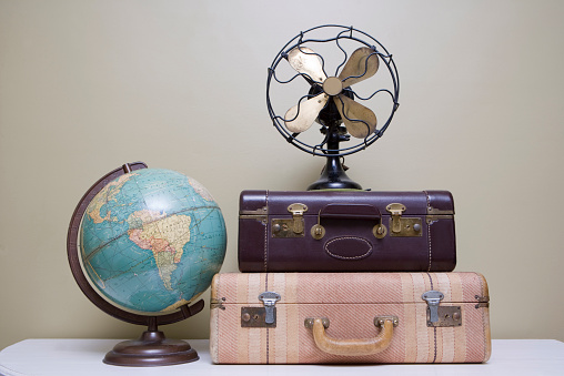 Selection of various vintage, antique and retro items including two suitcases, a globe and a fan that sit on a white table