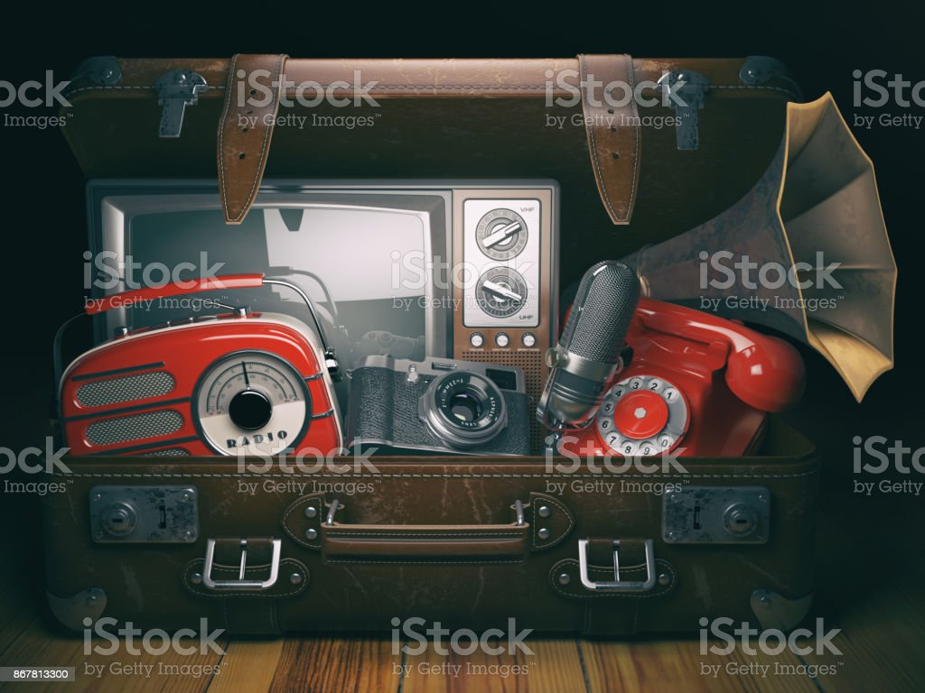 Vintage suitcase with old obsolete electronic equipment set. Retro technology concept background. Radio, tv set, telephone camera microphone and gramophone. stock photo