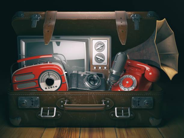 vintage koffer mit alten veraltete elektronische geräte eingestellt. retro-technologie-konzept-hintergrund. radio, tv-set, telefon kameramikrofon und grammophon. - nostalgie telefon stock-fotos und bilder