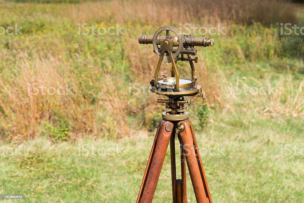 Vintage Surveyor's Level (Transit, Theodolite) with Tripod in a field. stock photo