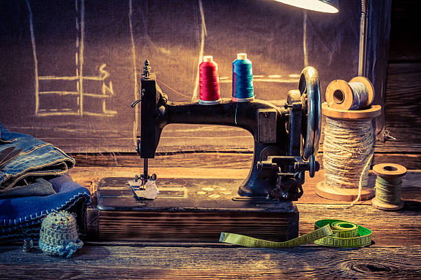 vintage tailor workshop with sewing machine, cloth and scissors - sewing machine needle stock photos and pictures