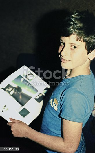 vintage color image of a teenager reading a magazine.
